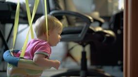 Λίγο παιδί πηδά με τη βοήθεια του ειδικού εξοπλισμού για τα παιδιά φιλμ μικρού μήκους
