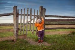 Λίγο παιδί που ανοίγει τις παλαιές πύλες Η προσέγγιση θύελλας στοκ φωτογραφίες