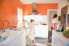 Λίγο παιδί που εξετάζει την ταμπλέτα δίπλα στη μητέρα στην κουζίνα στοκ φωτογραφίες