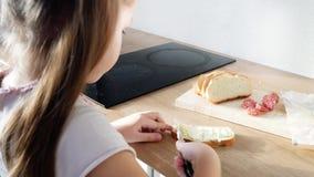 Λίγο παιδί που κατασκευάζει το σάντουιτς με το βούτυρο και το λουκάνικο φιλμ μικρού μήκους