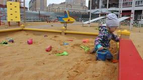 Λίγο παιδί που παίζει με τις φόρμες στο Sandbox στην παιδική χαρά φιλμ μικρού μήκους
