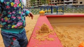 Λίγο παιδί που παίζει με τις φόρμες στο Sandbox στην παιδική χαρά απόθεμα βίντεο