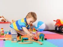 Λίγο παιδί που παίζει με τον ξύλινο σιδηρόδρομο Στοκ εικόνες με δικαίωμα ελεύθερης χρήσης