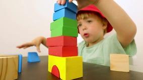 Λίγο παιδί που παίζει με τους φραγμούς φιλμ μικρού μήκους