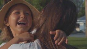 Λίγο παιδί που τρέχει στα αγκαλιάσματα μητέρων της ` s στο πάρκο σε σε αργή κίνηση φιλμ μικρού μήκους