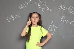 Λίγο παιδί σχολείου και μαθηματικοί τύποι στοκ εικόνες