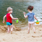 Λίγο παιχνίδι αγοριών και κοριτσιών μικρών παιδιών μαζί με τα παιχνίδια άμμου πλησίον Στοκ εικόνες με δικαίωμα ελεύθερης χρήσης