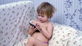 Λίγο παιδί με το τηλέφωνο στο κρεβάτι απόθεμα βίντεο