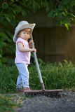 Λίγο παιδί που μαζεύει με τη τσουγκράνα επάνω το χώμα και που προετοιμάζεται για τη φύτευση Στοκ Φωτογραφίες