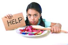 Λίγο παιδί που τρώει τη γλυκιά ζάχαρη στο spoo ζάχαρης εκμετάλλευσης πιάτων καραμελών στοκ φωτογραφίες