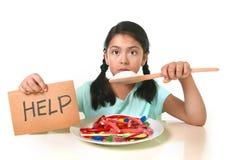 Λίγο παιδί που τρώει τη γλυκιά ζάχαρη στο spoo ζάχαρης εκμετάλλευσης πιάτων καραμελών στοκ εικόνες