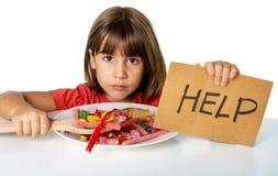 Λίγο παιδί που τρώει τη γλυκιά ζάχαρη στο spoo ζάχαρης εκμετάλλευσης πιάτων καραμελών Στοκ Φωτογραφία