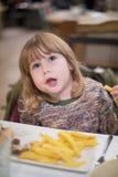 Λίγο παιδί που τρώει τις τηγανιτές πατάτες με το χέρι Στοκ Εικόνες