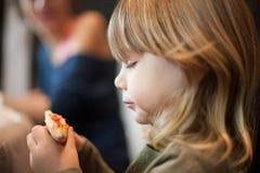 Λίγο παιδί που φαίνεται άκρη πιτσών πριν από το τρώει Στοκ φωτογραφία με δικαίωμα ελεύθερης χρήσης