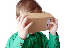 Λίγο παιδί χρησιμοποιεί την εικονική πραγματικότητα (χαρτόνι VR) στο άσπρο υπόβαθρο Στοκ Φωτογραφία