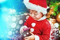 Λίγο παιδί santa που ελέγχει το δώρο Στοκ φωτογραφία με δικαίωμα ελεύθερης χρήσης
