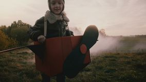 Λίγο πειραματικό κορίτσι που τρέχει στο αεροπλάνο χαρτονιού διασκέδασης με τον καπνό χρώματος πίσω στον καταπληκτικό τομέα ηλιοβα απόθεμα βίντεο