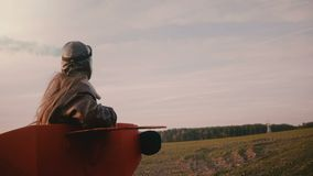 Λίγο πειραματικό κορίτσι που τρέχει στο κοστούμι αεροπλάνων διασκέδασης με τον καπνό χρώματος υπό εξέταση στον καταπληκτικό τομέα φιλμ μικρού μήκους