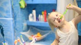 Λίγο πορτρέτο προσώπου κοριτσιών παιδιών που βουρτσίζει τα δόντια της με μια οδοντόβουρτσα στο λουτρό το πρωί φιλμ μικρού μήκους