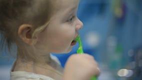 Λίγο πορτρέτο προσώπου κοριτσιών παιδιών που βουρτσίζει τα δόντια της με μια οδοντόβουρτσα στο λουτρό το πρωί απόθεμα βίντεο