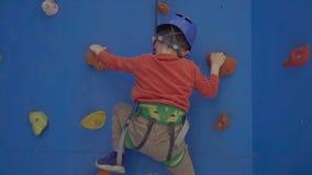 Λίγο προσχολικό αγόρι, που αναρριχείται στον τοίχο στο εσωτερικό, έχοντας τη διασκέδαση, ενεργά παιδιά απόθεμα βίντεο