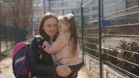Λίγο πρώτος-γκρέιντερ στα χέρια της μητέρας της Το Mom φέρνει λίγη κόρη στα χέρια του σχολείου τους απόθεμα βίντεο