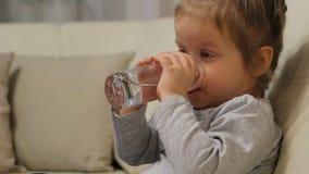 Λίγο πόσιμο νερό παιδιών από μια συνεδρίαση γυαλιού σε έναν καναπέ στο δωμάτιο απόθεμα βίντεο