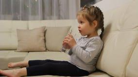 Λίγο πόσιμο νερό παιδιών από μια συνεδρίαση γυαλιού σε έναν καναπέ στο δωμάτιο φιλμ μικρού μήκους