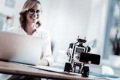 Λίγο ρομπότ που κρατά το σύγχρονο smartphone Στοκ Εικόνα