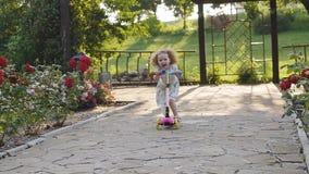 Λίγο σγουρό κορίτσι με το πάθος και το γέλιο οδηγά στο μηχανικό δίκυκλο απόθεμα βίντεο