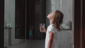 Λίγο σγουρό κορίτσι παιδιών ξεπλένει το στόμα της με το νερό στο λουτρό, πλάγια όψη φιλμ μικρού μήκους