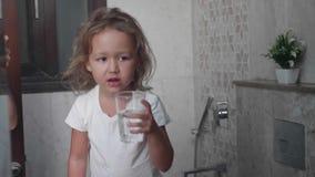 Λίγο σγουρό κορίτσι παιδιών ξεπλένει το στόμα της με το νερό φιλμ μικρού μήκους