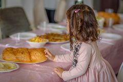 Λίγο σγουρό κορίτσι που τοποθετεί challah πασπαλίζει με ψίχουλα σε έναν πίνακα για το γεύμα Shabbat στοκ εικόνα με δικαίωμα ελεύθερης χρήσης