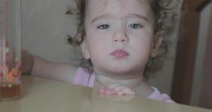 Λίγο σγουρό κορίτσι που τρώει το αρτοποιείο αχύρων απόθεμα βίντεο