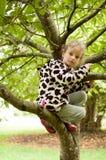 Λίγο σγουρό κορίτσι σε ένα επισημασμένο δέρας και λαστιχένιες μπότες κάθεται σε ένα δέντρο Διακοπές στο χωριό, σωματική δραστηριό στοκ εικόνα