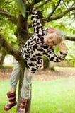 Λίγο σγουρό κορίτσι σε ένα επισημασμένο δέρας και λαστιχένιες μπότες κάθεται σε ένα δέντρο Διακοπές στο χωριό, σωματική δραστηριό στοκ φωτογραφίες με δικαίωμα ελεύθερης χρήσης
