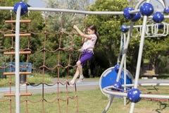 Λίγο σχολικό κορίτσι αρχαρίων που παίζει στην παιδική χαρά στοκ φωτογραφίες