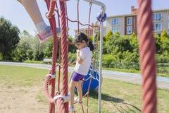 Λίγο σχολικό κορίτσι αρχαρίων που παίζει στην παιδική χαρά στοκ εικόνες