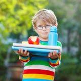 Λίγο σχολικό αγόρι με τα βιβλία, το μπουκάλι μήλων και ποτών Στοκ φωτογραφίες με δικαίωμα ελεύθερης χρήσης