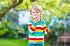 Λίγο σχολικό αγόρι με τα βιβλία, το μπουκάλι μήλων και ποτών Στοκ φωτογραφία με δικαίωμα ελεύθερης χρήσης