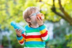 Λίγο σχολικό αγόρι με τα βιβλία, το μπουκάλι μήλων και ποτών Στοκ εικόνα με δικαίωμα ελεύθερης χρήσης