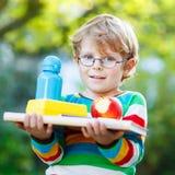 Λίγο σχολικό αγόρι με τα βιβλία, το μπουκάλι μήλων και ποτών Στοκ Εικόνα