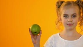 Λίγο υγιές παιδί που κρατά το φρέσκο πράσινο μήλο και που χαμογελά στη κάμερα, βιταμίνες φιλμ μικρού μήκους