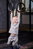 Λίγο φίλαθλο αγόρι στην γκρίζα sportwear ένωση στα γυμναστικά δαχτυλίδια στη γυμναστική Στοκ Εικόνες