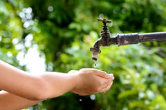 Λίγο χέρι περιμένει την πτώση νερού από τη στρόφιγγα Στοκ Εικόνα