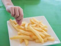 Λίγο χέρι που παίρνει τις τηγανιτές πατάτες Στοκ Φωτογραφίες