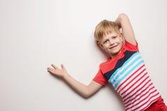 Λίγο χαμογελώντας αγόρι στην μπλούζα που απομονώνεται στο άσπρο υπόβαθρο Πορτρέτο στούντιο στοκ εικόνα με δικαίωμα ελεύθερης χρήσης