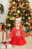 Λίγο χαμογελώντας θηλυκό παιδί που φορά την κόκκινη συνεδρίαση φορεμάτων στο πάτωμα κοντά στα δώρα και το χριστουγεννιάτικο δέντρ Στοκ Φωτογραφίες