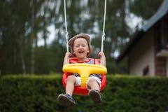 Λίγο χαμογελώντας αγόρι που έχει τη διασκέδαση και που ταλαντεύεται στο υπαίθριο playgroun Στοκ Φωτογραφία