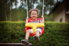 Λίγο χαμογελώντας αγόρι που έχει τη διασκέδαση και που ταλαντεύεται στο υπαίθριο playgroun Στοκ Εικόνα